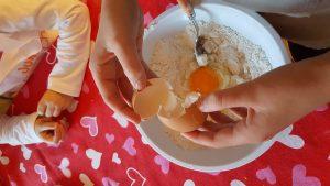bambina che apre le uova per fare la torta