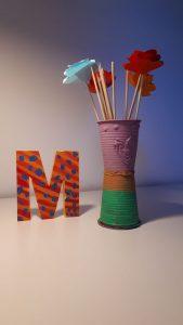 vaso di palstica e fiori di carta e iniziale delle lettera M colorati e fatti a mano
