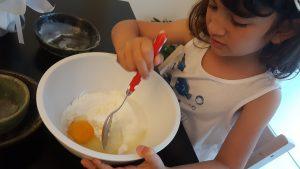 bambina che impasta la torta e le uova