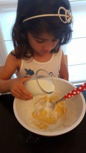 bambina che versa il latte in una torta