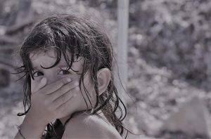 bambina che si copre con la mano la bocca