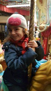 bambina sulla giostra che sorride