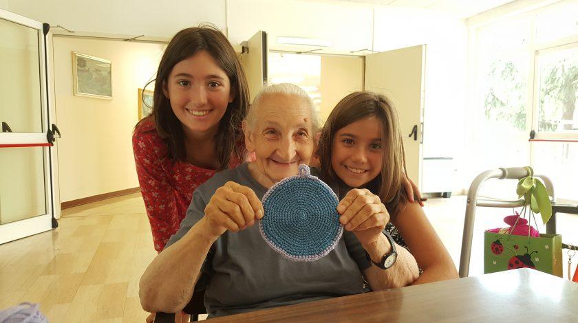 signora anziana che mostra una presina di uncinetto con bambine vicino