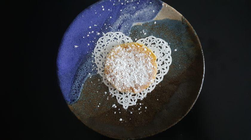 mini pancake alla nutella con zucchero a velo su piatto di ceramica