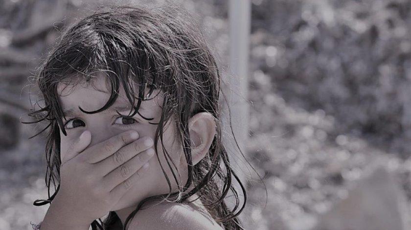primo piano di bambina con mano che copre la bocca
