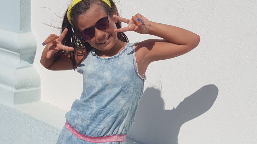 bambina con occhiali da sole e vestito azzurro