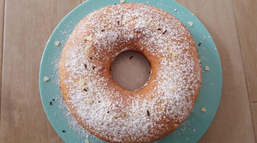 foto di un ciambellone con zucchero a velo e granella di cioccolato su un piatto di ceramica