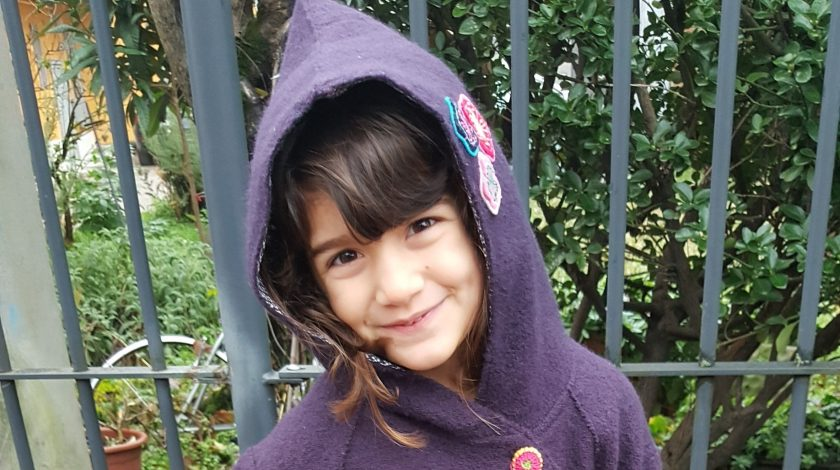 bambina di 5 anni con cappotto viola e con il cappuccio in testa